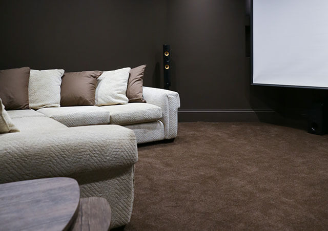 basement converted into home cinema.sofa, speaker, projector